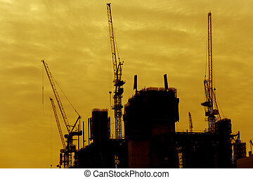 silhouette of Construction site with cranes in yellow tone