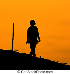Silhouette of construction workers on scaffold working under...