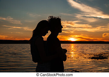 Silhouette of couple hugging near the sea on sunset