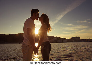 Silhouette of couple in love kissing and watching on the sunset