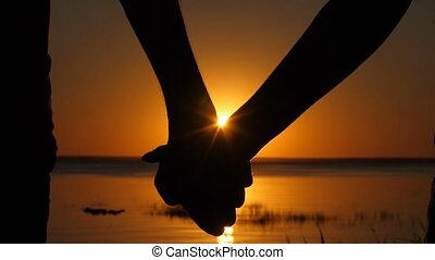 Silhouette of couple joining hands over sunset - Close-up of...