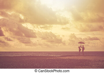 Silhouette of couple people or tourist standing on the beach in sunset time. Warm tone and vintage filter effect