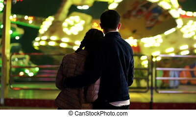 Silhouette of couple, which standing back to camera and watching rotation of attractions in amusement park. Lovers spending time together on date at night. Millennial lifestyle.