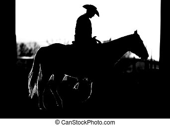 Black and white silhouette of an authentic cowboy riding his horse.