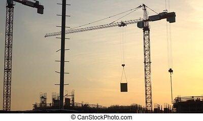 Silhouette of crane transferring concrete plate over...