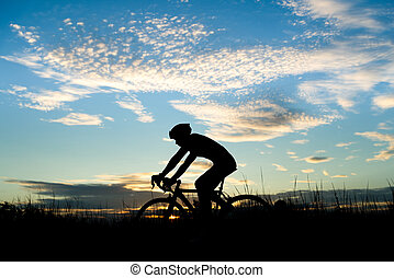 Silhouette of cyclist riding a road bike on open road in evening during sunset. Sports and outdoor activities concept.