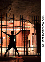 Silhouette of dancing girl in the dark, she open her legs and hands and holding lattice