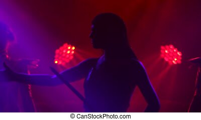 Silhouette of dancing Joan of Arc on stage in a dark studio ...