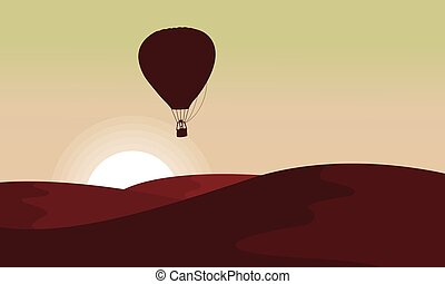Silhouette of desert with air balloon in the sky