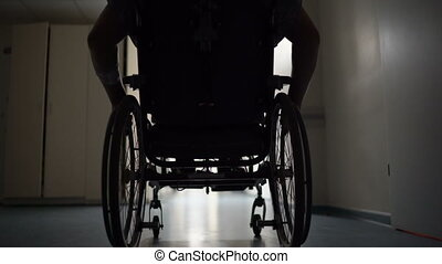 Silhouette of disabled man pushes himself in wheelchair down hospital corridor