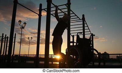 Silhouette of disabled young man pulled up on the crossbars...