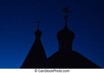 Silhouette of domes with crosses of the Orthodox church against the blue sky in the evening