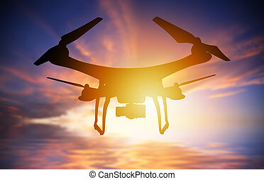 Silhouette of drone with digital camera flying in a sunset sky