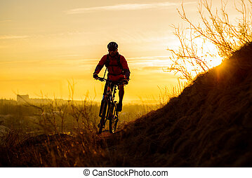 Silhouette of Enduro Cyclist Riding the Mountain Bike on the Rocky Trail at Sunset. Active Lifestyle Concept. Space for Text.