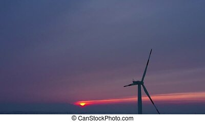 Silhouette of energy producing wind turbines at sunset,...