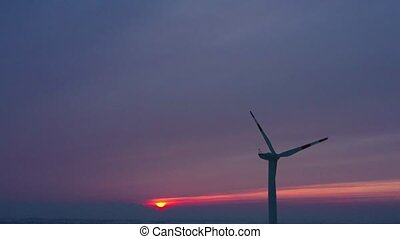 Silhouette of energy producing wind turbines at sunset, Poland