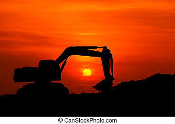 silhouette of excavator machine with sunset