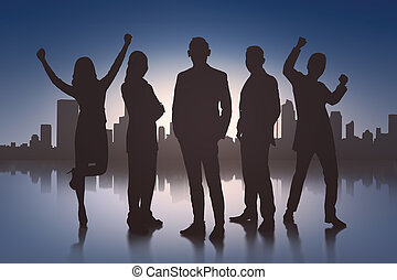 Silhouette of excited business people with cityscape