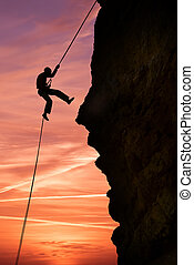 Silhouette of extreme rock climber against beautiful sunset