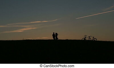 Silhouette of Fabulous Couple With Tandem Bicycles Jumping...