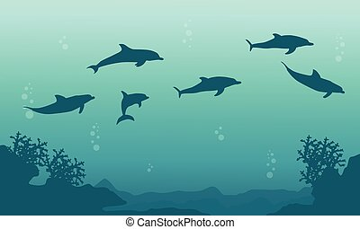 Silhouette of family dophin on sea landscape