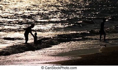 Silhouette of family fun on beach
