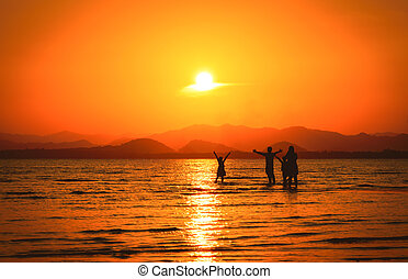 Silhouette of family on the beach at sunset.