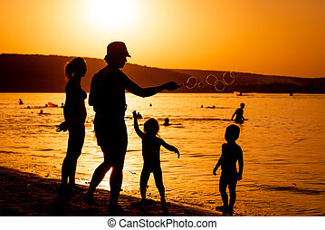 silhouette of family playing with soap bubbles near water at sunset