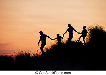 Silhouette of Family Running Through the Sand Dunes