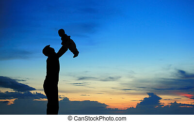 Silhouette of father and child on summer sunset