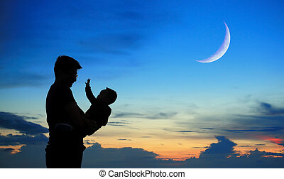 Silhouette of father and child on sunset