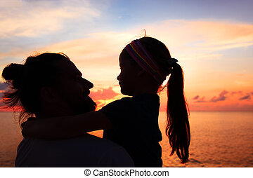 Silhouette of father and daughter on the beach at dusk.