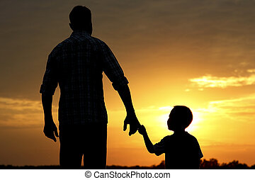 silhouette of father and son on sunset