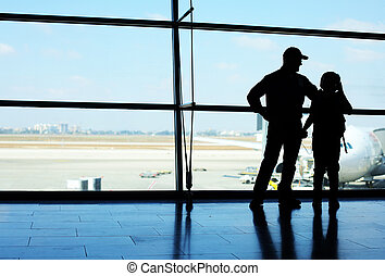 Silhouette of father and son standing in front of the window in airport