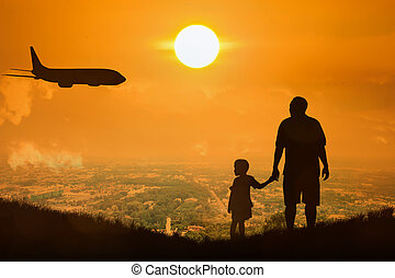 silhouette of father and son standing on the town sunset background