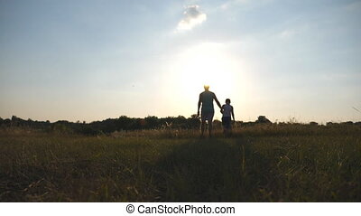 Silhouette of father and son walking on the field at sunset and holding hands of each other. Happy family spending time together outdoor. Active lifestyle. Slow motion Rear back view