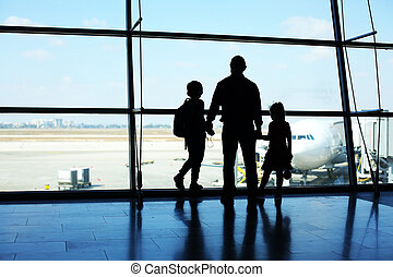 Silhouette of father and two kids standing in front of the window in airport