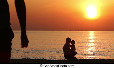 silhouette of father cleaning nose to kid on beach at sunrise