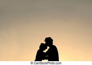 Silhouette of Father Kissing Young Child on Forehead
