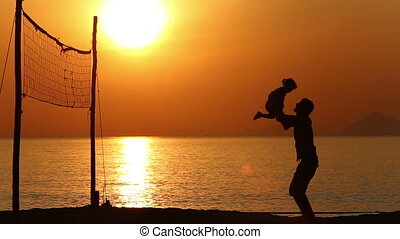silhouette of father playing with kid on beach at sunrise