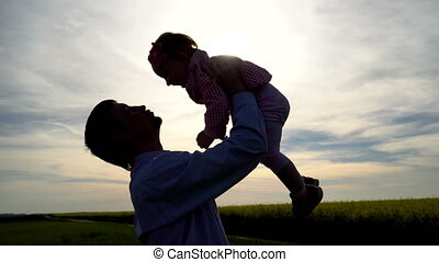 Silhouette of father raising his daughter
