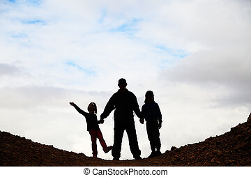 silhouette of father with two kids