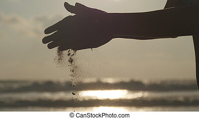 Silhouette of female hand pouring sea sand through her fingers at sunset against an ocean background. Arm of young woman with sand strewed or falling from it. Grit drizzling from fist of girl. Closeup