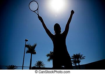 Silhouette of female tennis match winner
