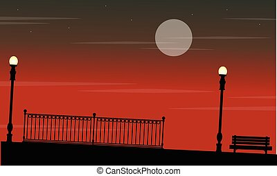 Silhouette of fence with lamp on the street at night