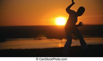 Silhouette of fighter performing capoeira tricks on the hill at summer sunset