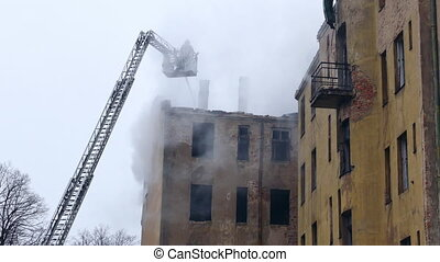 Silhouette of firefighter on turntable ladder fighting fire on burning abandoned building