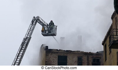 Silhouette of firefighter on turntable ladder fighting fire on burning abandoned building. Time stretched video
