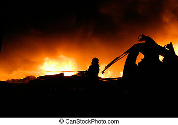 Silhouette of Firemen fighting a raging fire