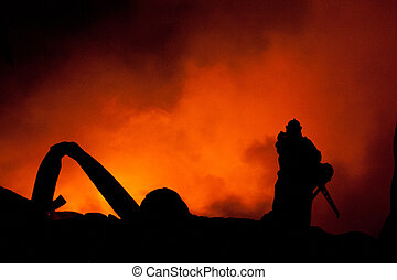 Silhouette of Firemen fighting a raging fire with huge...
